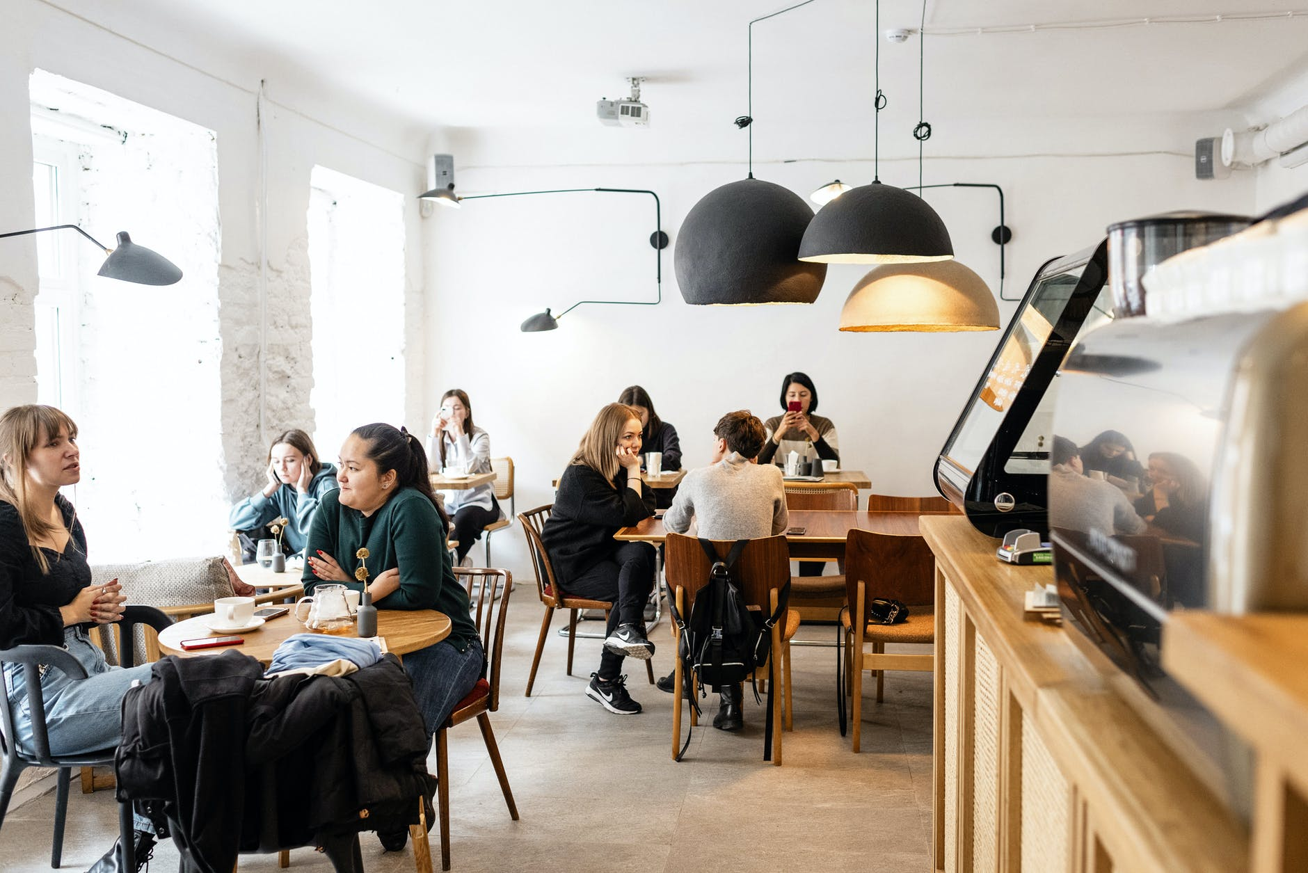 group of diverse friends sitting in modern cafe